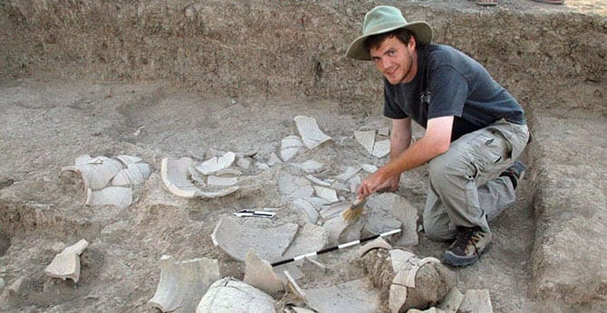 student in hat at dig with pottery shards in dirt