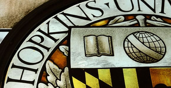 stained glass window with university seal