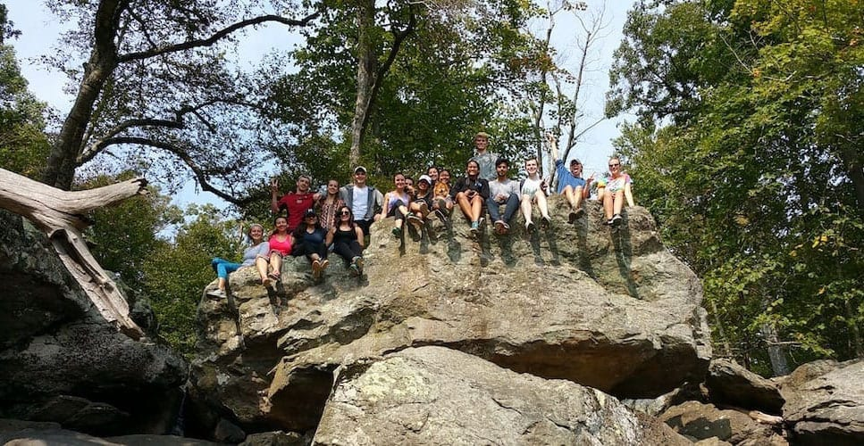 15 students sitting high up on rock formation in woods