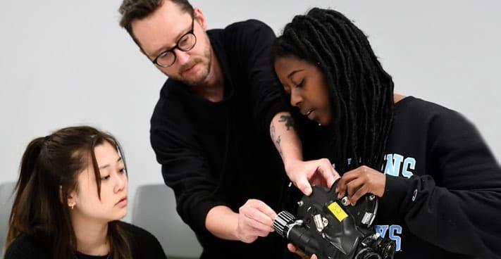 Professor Matt Porterfield shows 2 undergraduate students how to adjust camera lens