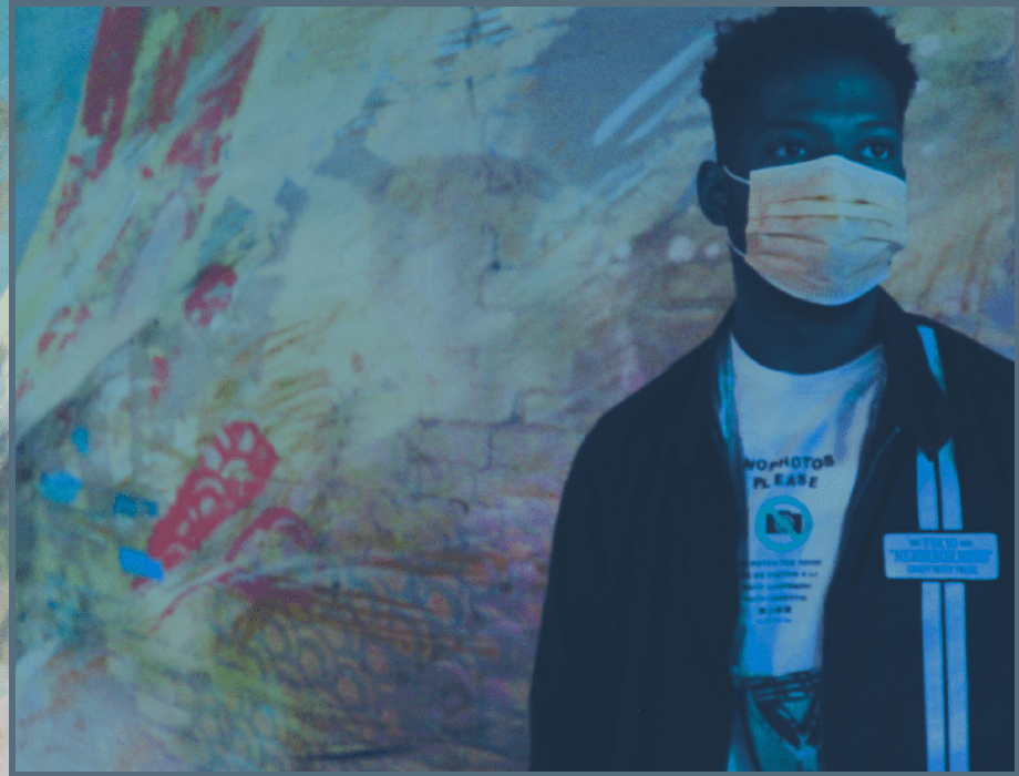 Ikenna with a mask in front of art