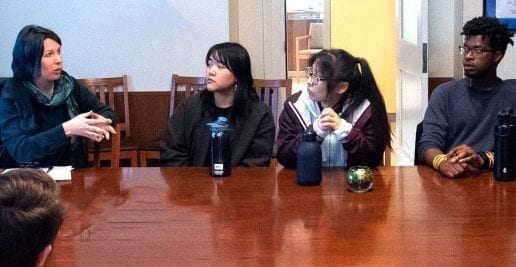 students at a table while professor talks