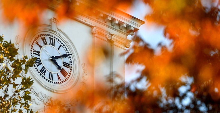 a view of Gilman Hall clock tower through fall leaves