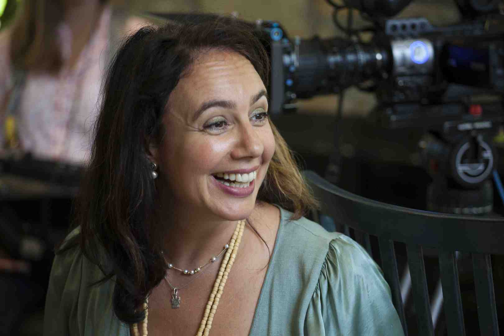 Bernadette Wegenstein laughing with a large camera behind her