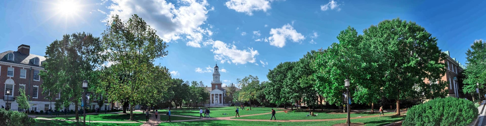 panoramic shot of green campus quad with sidewalks and brick buildings