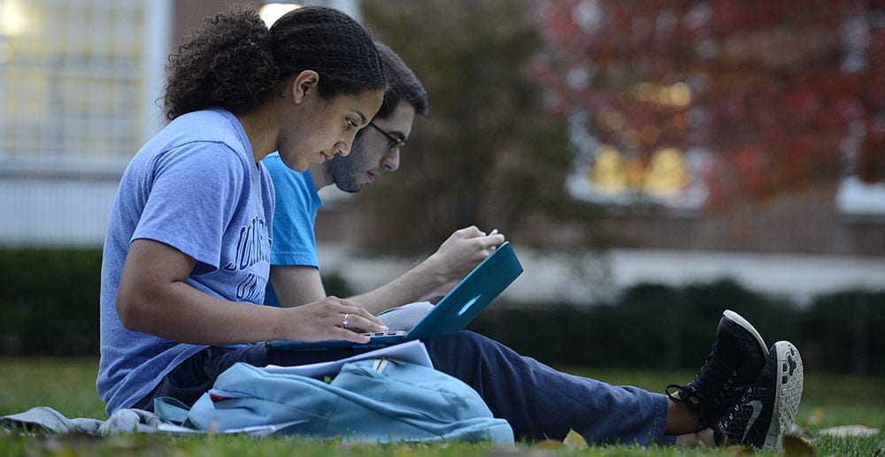 two students with laptops sitting on grass lawn with red trees in background