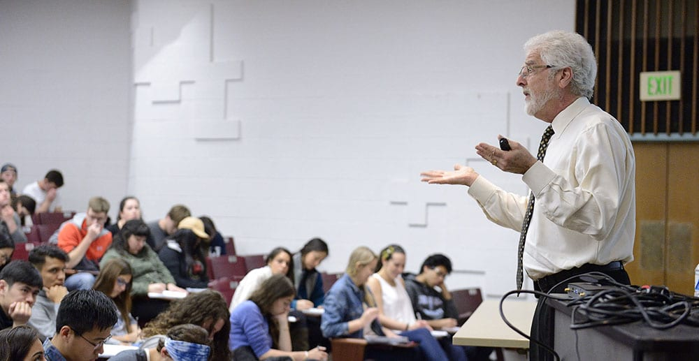 professor with microphone in front of large class