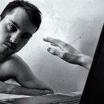 photo of man at laptop with hand reaching out of screen