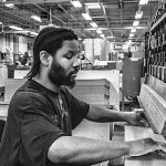 photo of man with braids at saw in factory