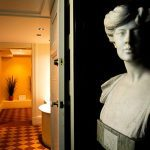 White marble bust of a woman in front of a hallway