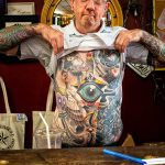 photo of man pulling up shirt to show tattooed stomach