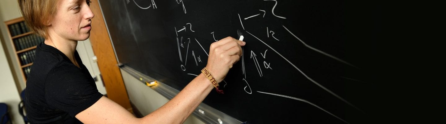 Math professor Emily Riehl works an equation at the blackboard