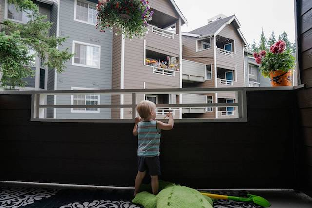 Boy on his balcony looking at the other homes in his apartment complex