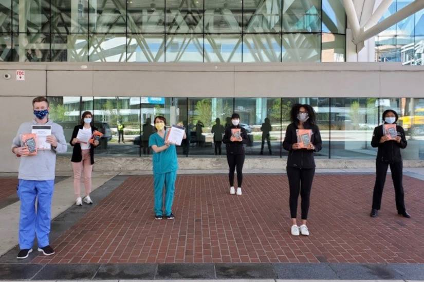 Five people stand spaced out holding iPads in front of medical building