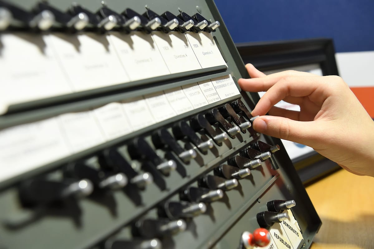 hand pushing buttons on vintage voting machine