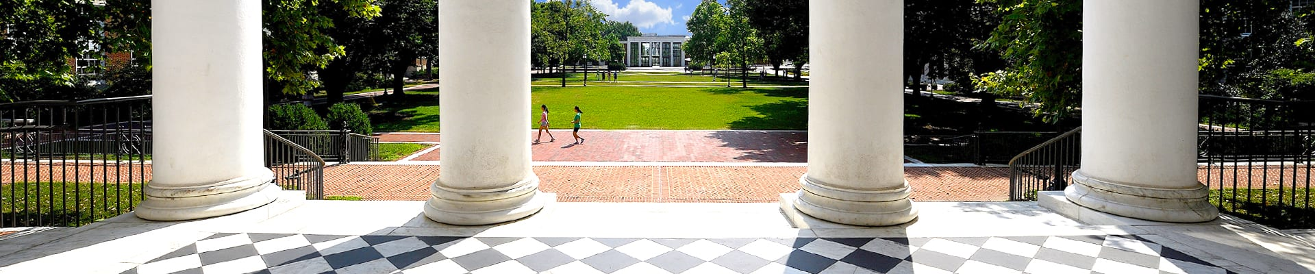 a view through Gilman Hall columns of the quad and library on a summer day