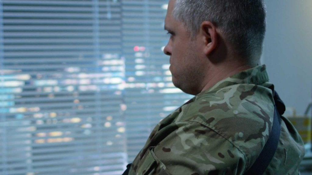 Seated man in fatigues looking at a window