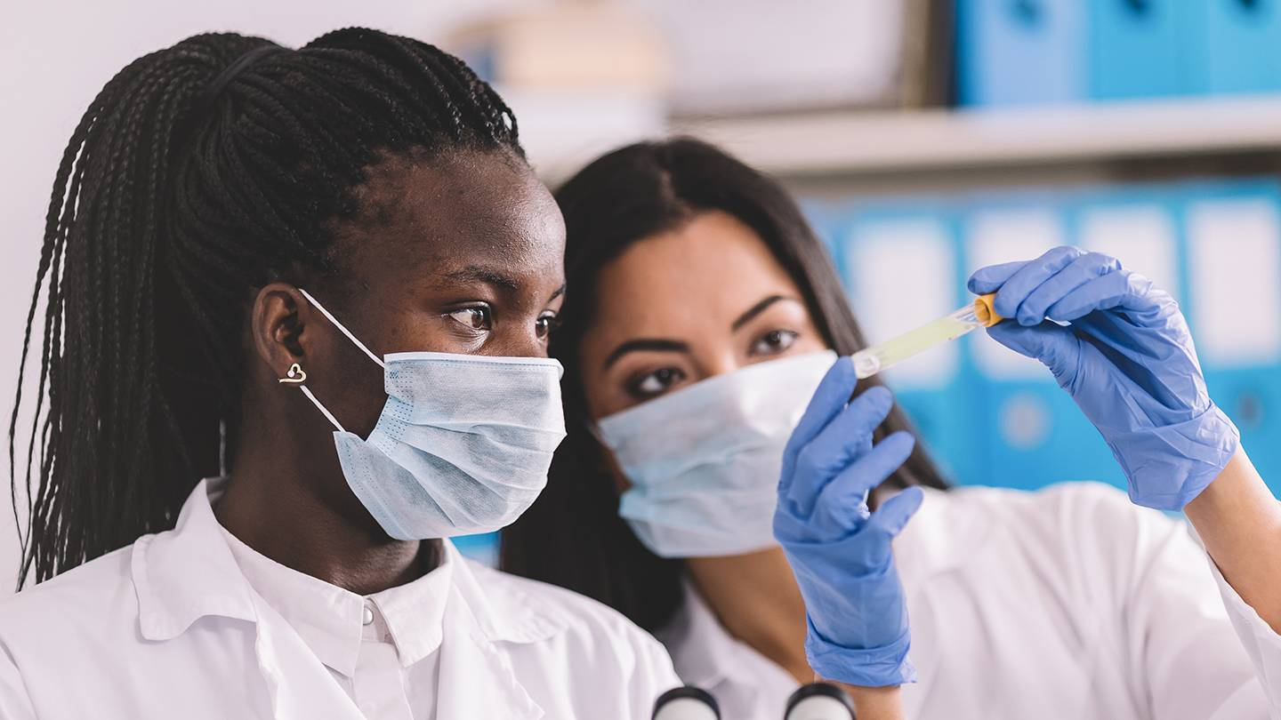 two women of color looking at a test tube while masked