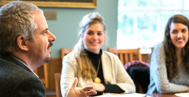 two students smiling at talking professor